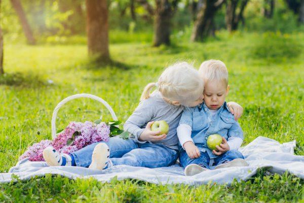 brother-sister-sitting-summer-meadow-600x400.jpg