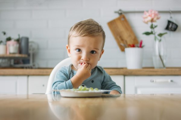 charming-little-baby-boy-eating-first-food-green-grape-bright-kitchen-home-600x400.jpg