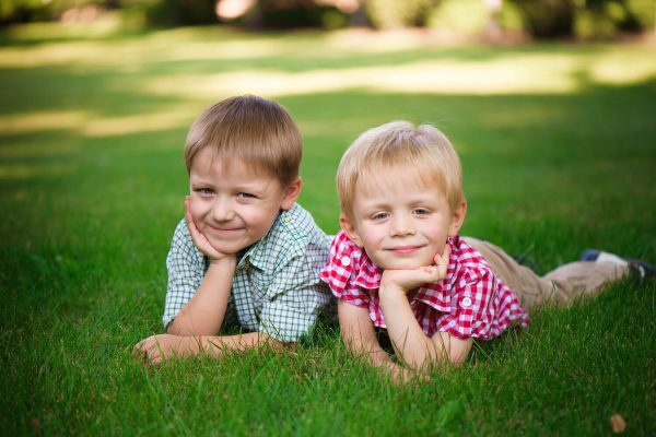 two-brothers-lying-grass-park-outdoors-smiling-600x400.jpg