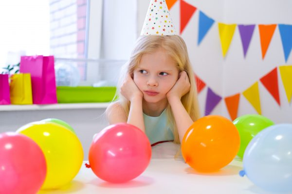 unhappy-blonde-caucasian-girl-with-boring-face-near-birthday-rainbow-cake-festive-colorful-background-bad-birthday-party-600x400.jpg